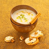 Cream of celeriac soup with croutons topped with cheese and walnuts