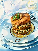 A layered cake with wild mushrooms and saffron sauce
