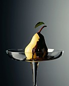 A pear with dark chocolate sauce on a glass plate
