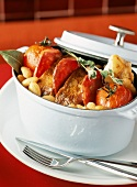 Casserole dish of roast veal with tomatoes and white beans