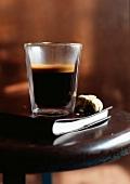 Glas Espresso und angebissener Keks auf einem Buch