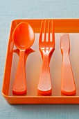 Orange plastic knife,fork and spoon