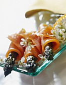 Green asparagus wrapped in sliced smoked salmon and garlic flowers