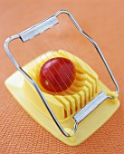 A tomato on an egg slicer