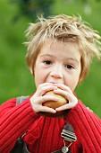 Kind beisst in einen Apfel
