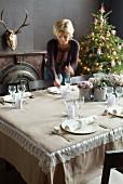 Frau deckt festlichen Tisch