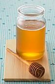 Pot of honey and wooden honey spoon