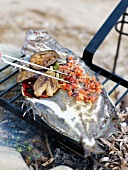 Grilling a fish and vegetables on the beach