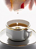 Adding artificial sweetener to a cup of expresso coffee