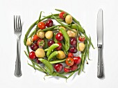 Frisches Obst und Gemüse in Form eines Tellers, zwischen Messer und Gabel