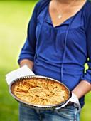 Woman holding an apple tart