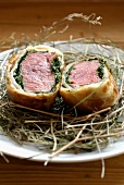 Beef fillet in pastry crust on a bed on hay