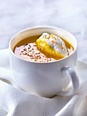 Cream of pumpkin and orange soup with whipped cream and orange zests