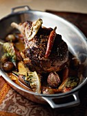 Veal chop cooked in a casserole dish with braised lettuce and carrots