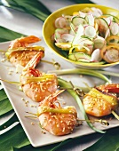 Shrimp kebabs with sesame seeds and cucumber and radish salad