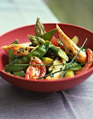 Sliced chicken breast with spring vegetables and herbs