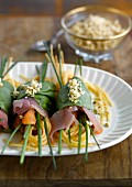 Spaghettis and raw ham wrapped in spinach leaves