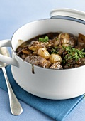 Casserole dish of capon cooked in red wine