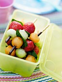 Mini fruit brochettes in a tupperware