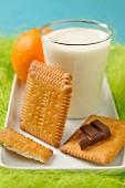Snack aus Butterkeksen, Milch, Schokolade und Orange