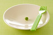 One pea in a plastic plate and fork