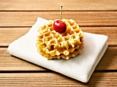 Three stacked waffles with a cherry on the top