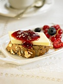 Manchego cheese on a slice of bread with summer fruit jam
