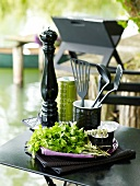 Fresh herbs and cooking implements on a table outdoors