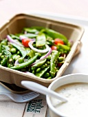 Take-away punnet of cooked green vegetables from the Whole Foods Market