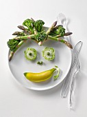 Plate of green vegetables and mini banana in the shape of a face
