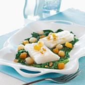 Thick pieces of cod with spinach,small onions and peanuts