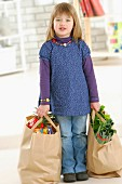 Young girl carrying bags of shopping