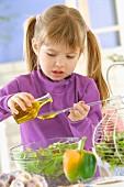 Kleines Mädchen rührt Salatdressing an