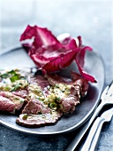 Cold sliced roast beef with mustard and herb sauce