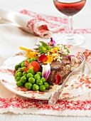 Veal steak with edible flowers and peas