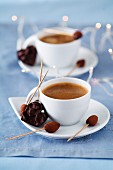Cups of coffee with almonds coated in chocolate and Rose des sable cakes