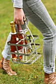 Person holding a metal bottle carrier with glasses and bottles of Champagne