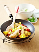 Chicken,cherry tomatoes and pineapple cooked in a wok