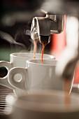 Espresso fliesst aus der Maschine in zwei Tassen
