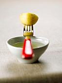 Half a potato on a fork on a bowl of olive oil