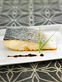 Oven-baked bass steak with black olive puree