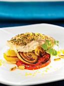 Oven-baked seabream coated in breadcrumbs, pan-fried tomatoes and onions