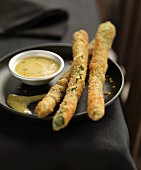 Fried asparagus coated in breadcrumbs with mustard sauce