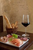 Dish of cold pork meats , bread sticks and a glass of red wine on a table in a restaurant