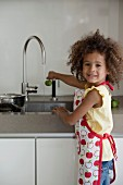 Young girl cleaning fruit under the tap water