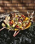 Auf Holzkohle stehender Teller mit Grillfleisch und Grillspiessen
