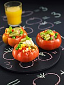 Raw tomatoes stuffed with peas, red peppers and sweet corn