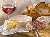 Camembert, dried sausage, bread and a glass of red wine