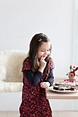 Young girl hesitating infront of a plate of chocolate biscuits