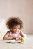 Kleines Mädchen schmollt vor einem Apfel